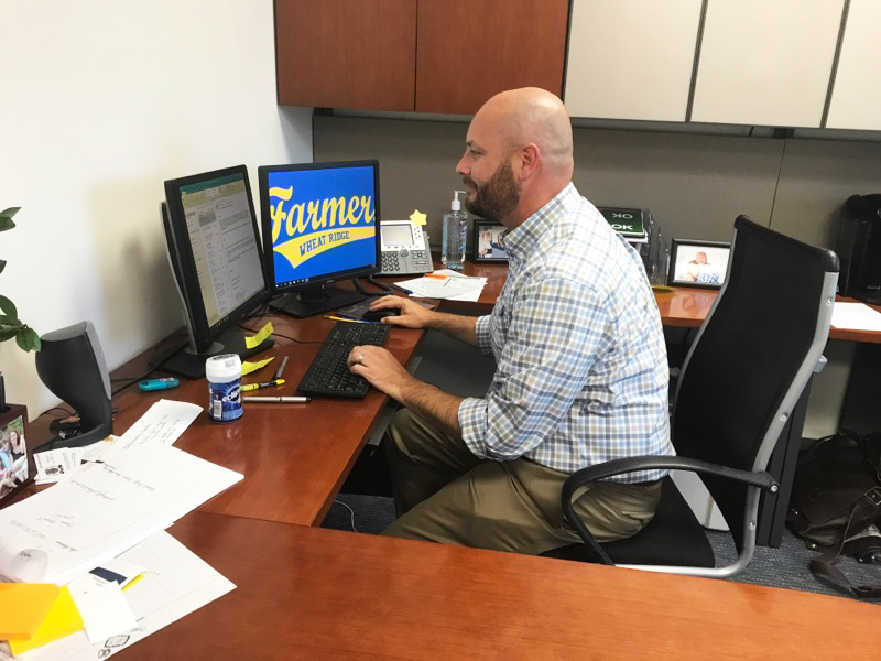 New principal Josh Cooley works in his offi ce. Cooley is one of three new administrators at Wheat Ridge this year. By Coleman Erickson