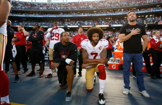 Colin Kaepernick kneeling at a football game during the anthem. courtesy of complex.com