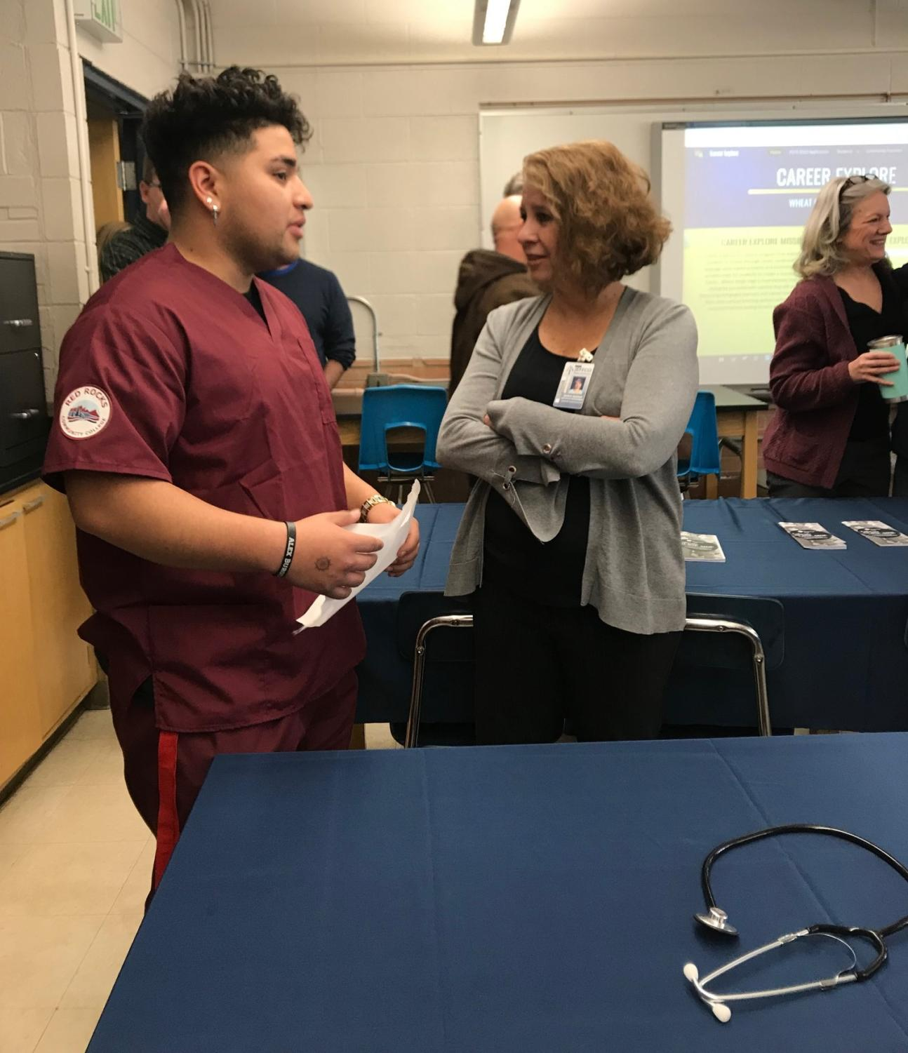 Senior Kenneth Godoy speaks to a district official on opening day of the lab.