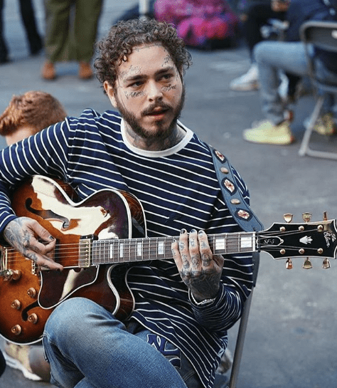 Post Malone playing the guitar.