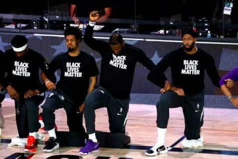Los Angeles Lakers players kneel for the national anthem.