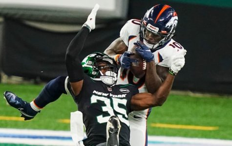 Broncos Rookie, Jerry Jeudy, catches the ball over Jets player, Dominique Williams